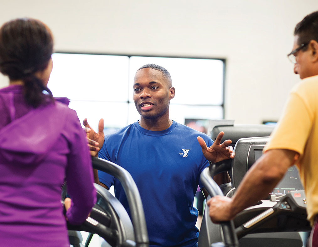 Personal Trainer assisting couple on the treadmills - attend your free new member orientation and assessment